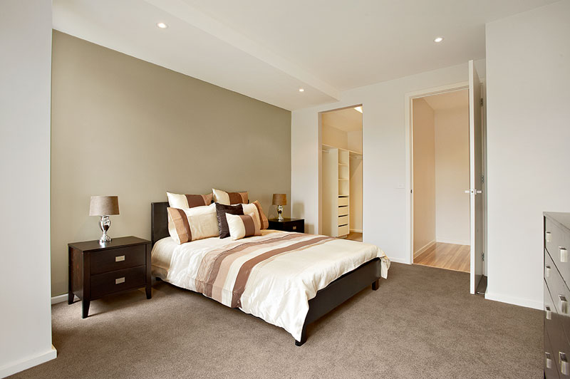 bedroom with fawn carpet, walk in robe, chocolate brown wooden bed and matching side draws