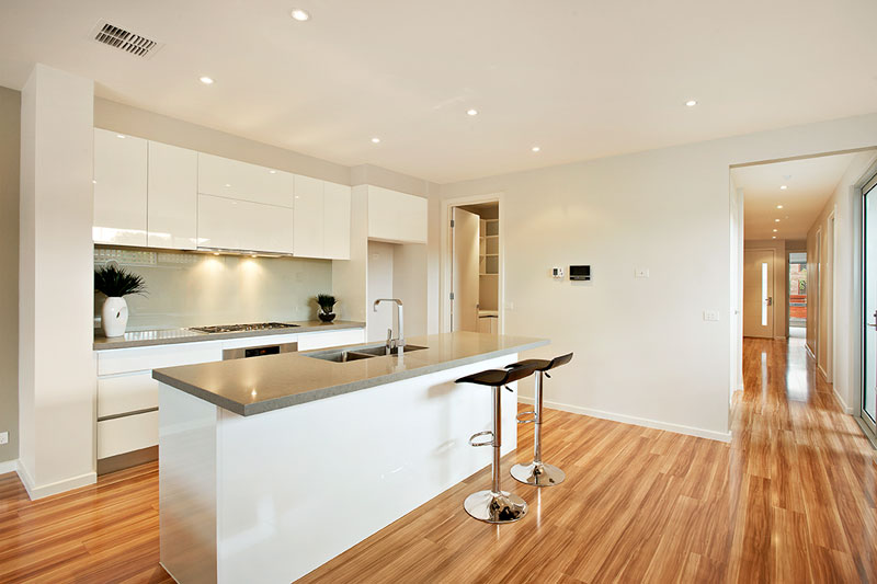 townhouse kitchen with light floor boards, light grey bench top and white walls and draws