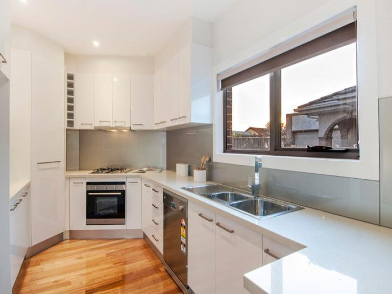 modern kitchen with white interior design and light polished floor boards. Modern appliances.