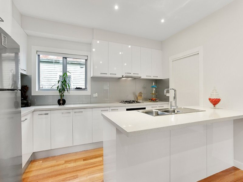 white kitchen with marble bench tops and light floor boards