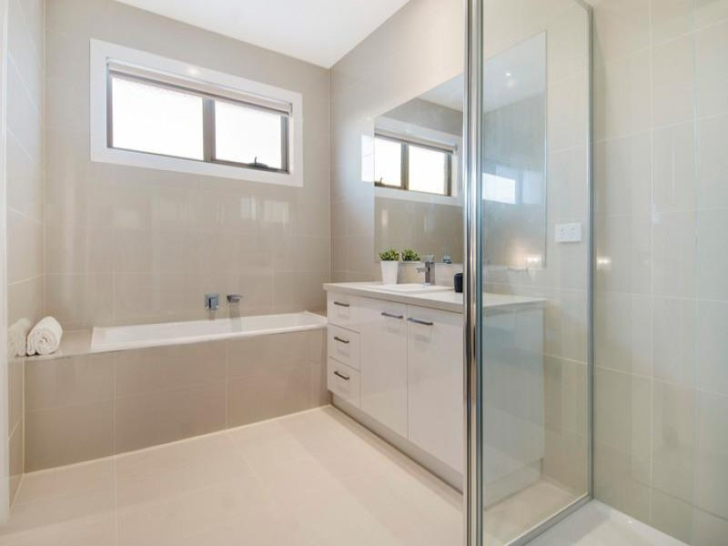 townhouse bathroom with large cream tiles and white vanit with bath.