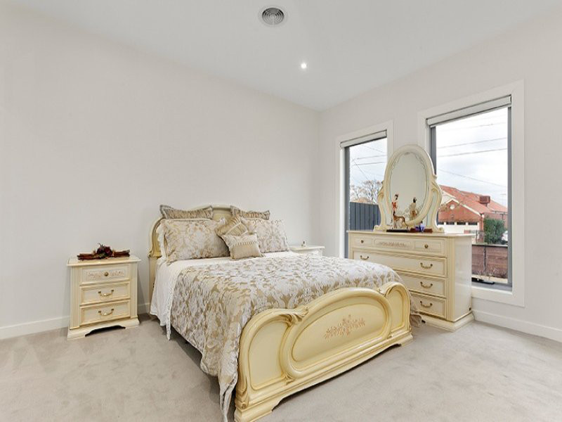 bedroom with light carpet, bedroom settee of gold and white tones and two long windows