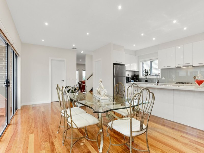 white kitchen with long centre bench parallel to stove and upper cupboards. Wooden floorboards and dining