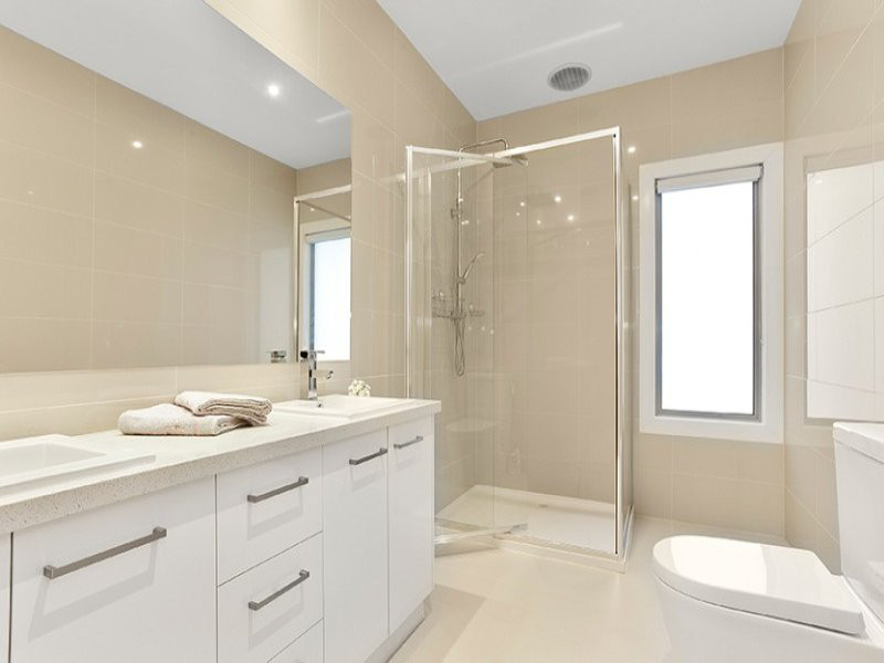 cream and white toned bathroom with dual modern basins and vanity on right, full glass shower recess at back and toilet on right