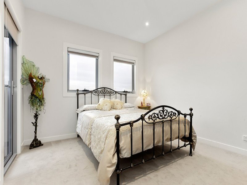 bedroom with door to balcony. Cream carpet and light grey walls and ornate bed with statue on left.