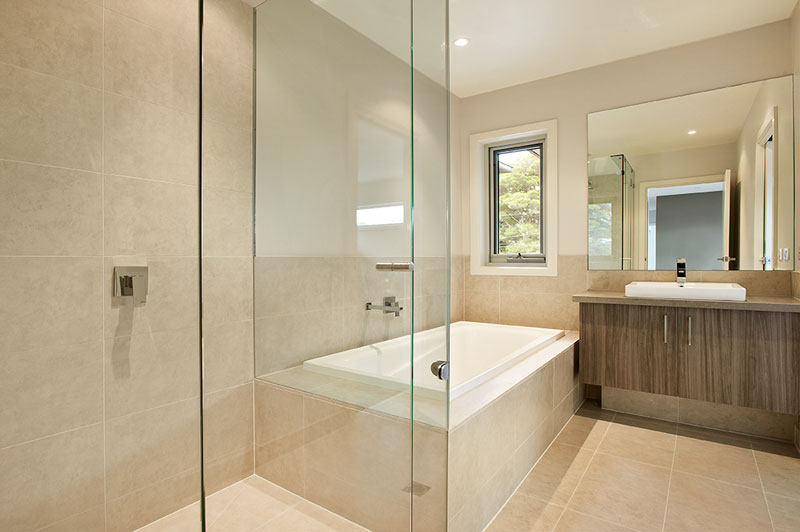 Bathroom with sand coloured large tiles throughout, wood grain vanity, rectangular bath and clear glass shower recess