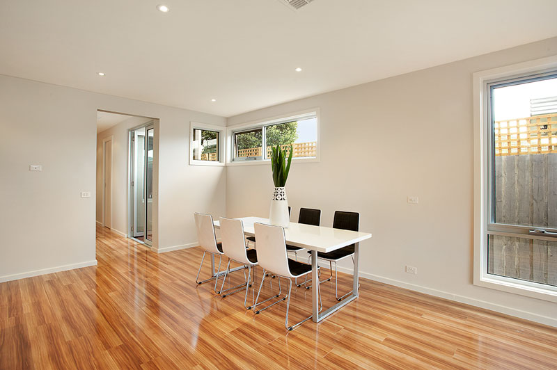 modern dining table, light polished floor boards and cream walls