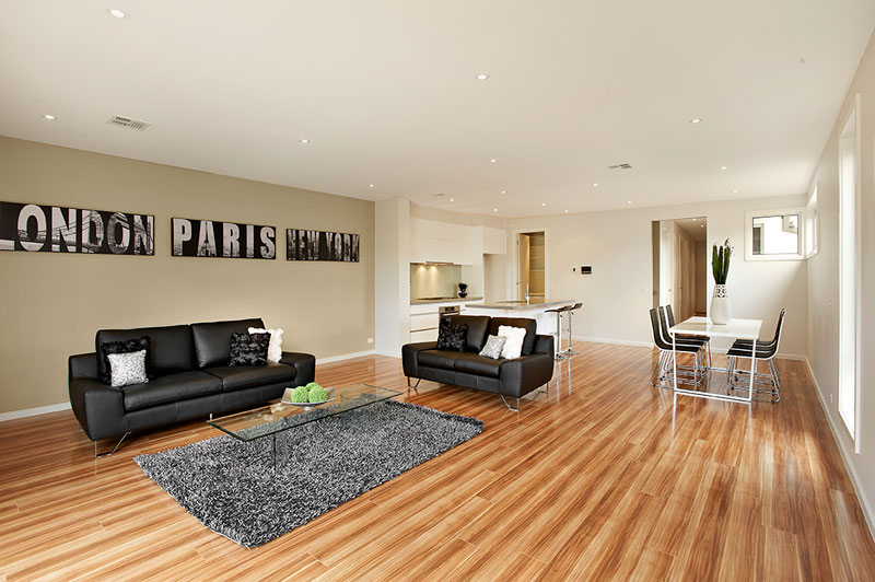 lounge area with art on wall, rug under glass table, open plan with couch, chair, table and chairs
