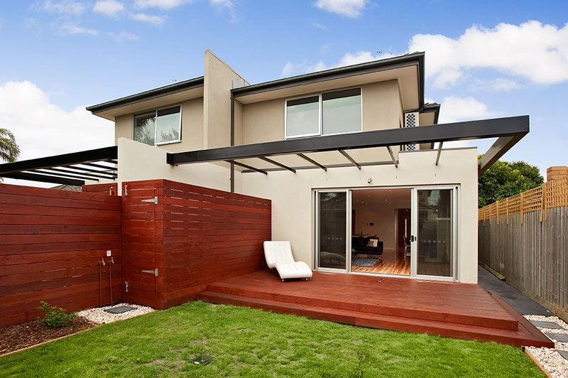 Lounge leading out to decking and backyard with grass