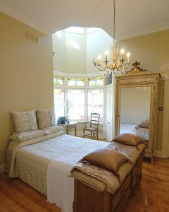 Queen Anne Style Home Renovations of bedroom with wooden floor boards, lead light bay windows