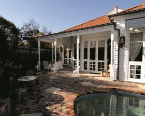 Queen Anne home renovation with el fresco area, brick flooring, glass doors and pool