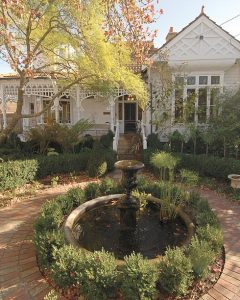 Queen Anne home renovated. White house, intricate verandah styling, brick work flooring and pond.