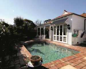 Queen Anne renovation backyard pool surrounde by brickwork, white weatherboard home with glass doors